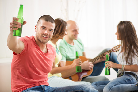 Close up of a young men smiling at home party with beer and cheers.  photo