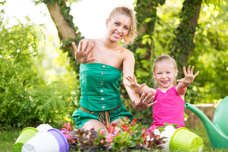 Beautiful mother and daughter planting flowers in the garden and showing dirty hands. photo