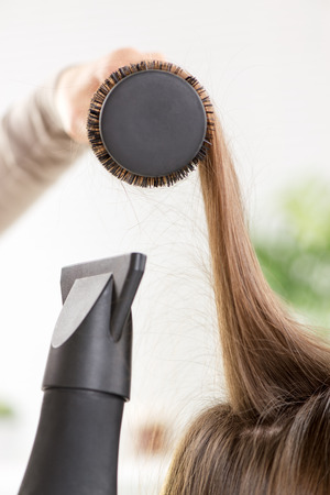 Drying long brown hair with hair dryer and round brush. photo