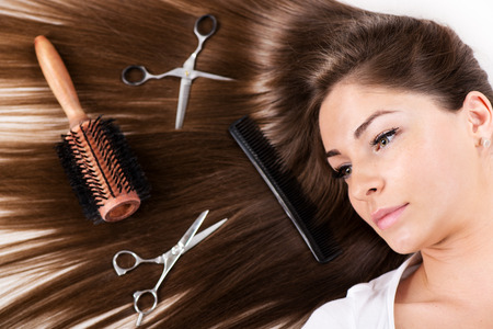 haircutting: Cute young woman with Beautiful healthy shiny hair and Haircutting Equipment. Stock Photo