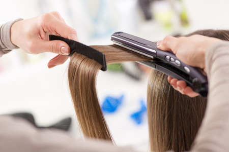 Hairdresser straightening long brown hair with hair irons.