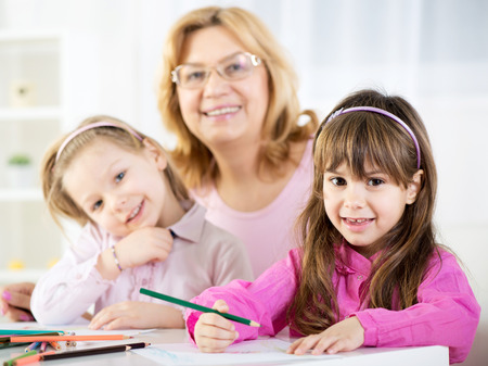 Two cute little girls drawing with colored pencils at home with Grandmother photo