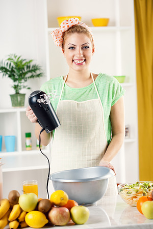 electric mixer: Beautiful young woman in the kitchen with electric mixer and bowl for mixing. Looking at camera.