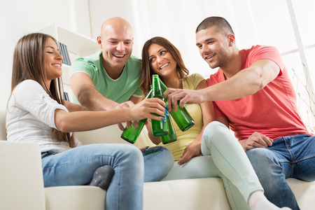 Friends enjoying with beer and cheers together at home party. photo
