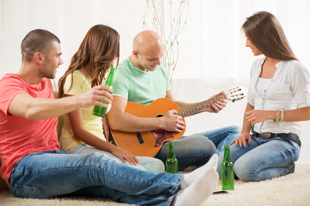 Four friends enjoying with guitar and beer together at the home party. photo