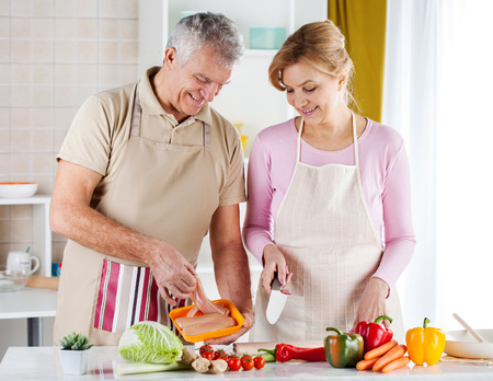 meat lover: Happy Senior Couple preparing food in the kitchen. Stock Photo