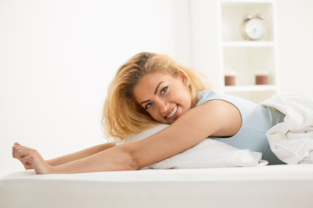 Young beautiful woman lying in bed in the morning. She is stretching. photo