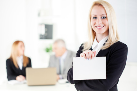 Beautiful young businesswoman holding Blank business card in the office. Looking at camera. Selective Focus. photo