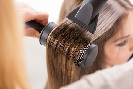Drying long brown hair with hair dryer and round brush. Close-up. Banco de Imagens