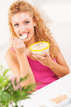 Beautiful young woman eating corn flakes for breakfast photo