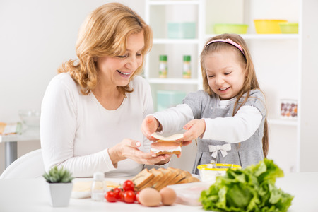 Cute little girl with Grandmother making a Sandwich in the kitchen.