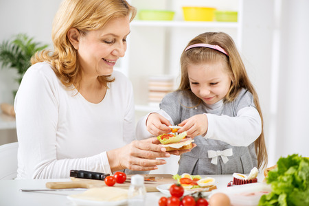 making a sandwich: Beautiful happy grandmother and her cute granddaughter making a Sandwich in the kitchen.