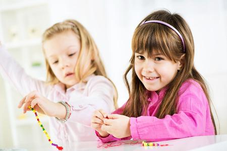 cute little girls: Dos ni�as lindas Haciendo joyer�a del grano en el hogar Foto de archivo