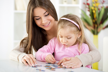 Mother and daughter playing at home. They assembling Jigsaw Puzzle. photo