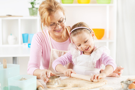 Beautiful happy grandmother and granddaughter a rolling pin together in the Kitchen.  photo