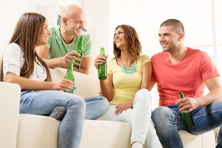 Four friends enjoying with beer together at the home party. photo