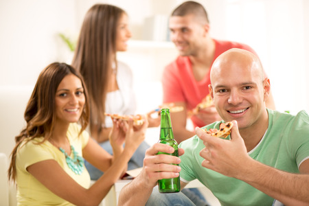Close up of a young men smiling and eating pizza and drinking bear with her friends in the background. photo