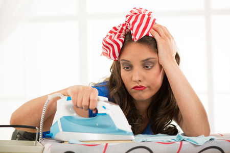 Depressed young housewife ironing clothes photo
