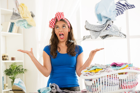 ironing: Depressed young housewife with basket laundry for ironing