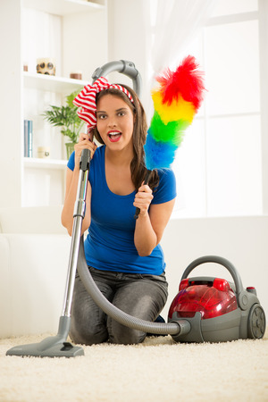 Portrait of a smiling young beautiful woman cleaning house. photo