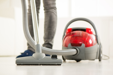 Woman vacuuming the house. Close-up with vacuum cleaner.