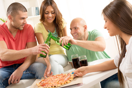 Friends enjoying eating pizza and drink a beer together at home party. photo