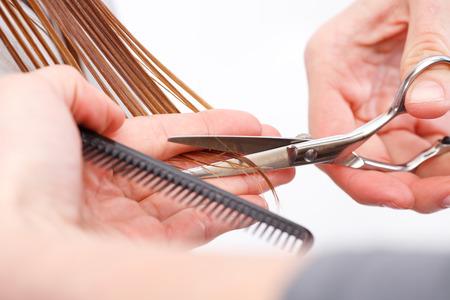 wet hair: Hairdresser cutting the hair of a blonde woman