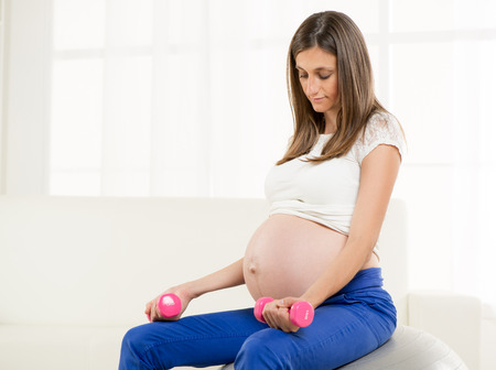 Happy Pregnant woman exercise weight on the Fitness Ball  photo