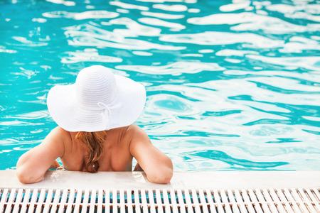 Young beautiful woman enjoying the sun in the pool photo