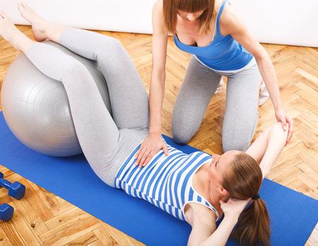 aide � la personne: jeune femme de remise en forme exercice avec un entra�neur personnel Banque d'images
