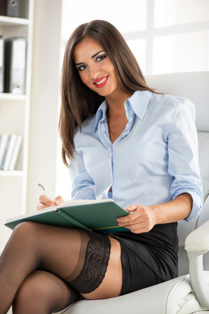 Beautiful Businesswoman sitting in the office. photo