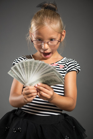 shutting: Pretty little girl smiling and looking with dollars. Studio shutting. Grey background.