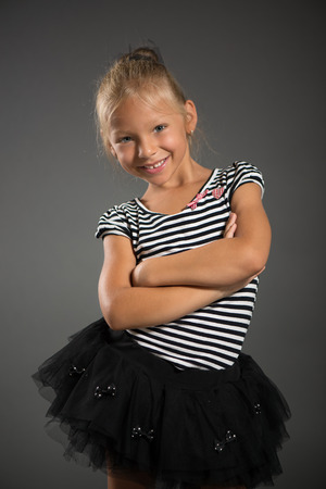 pretty little girl: Pretty little girl smiling and posing. Studio shutting. Grey background. Looking at camera.