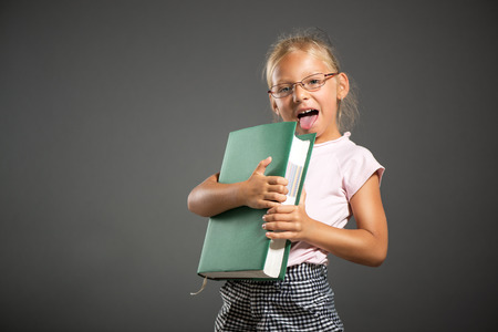 shutting: Cute little girl standing and holding large book. Studio shutting. Grey background. Looking at camera. Stock Photo