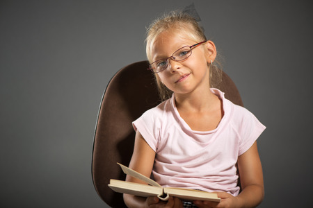 shutting: Tired Cute little girl holding book. Studio shutting. Grey background. Looking at camera.