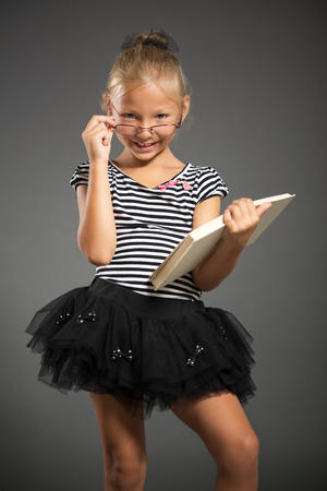 pretty little girl: Pretty little girl smiling and posing with book. Studio shutting. Grey background. Looking at camera.
