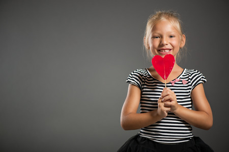 shutting: Pretty little girl smiling and posing with lollipop. Studio shutting. Grey background. Looking at camera.