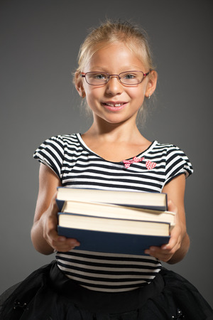 shutting: Cute little girl standing and holding books. Studio shutting. Grey background. Looking at camera.