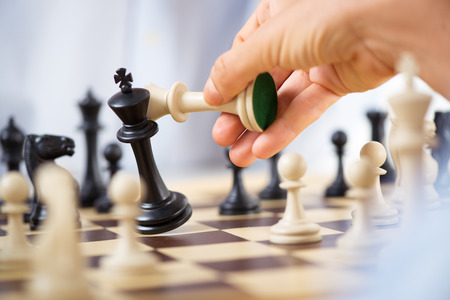 chess pieces: Man hand holding queen and king in checkmate position.