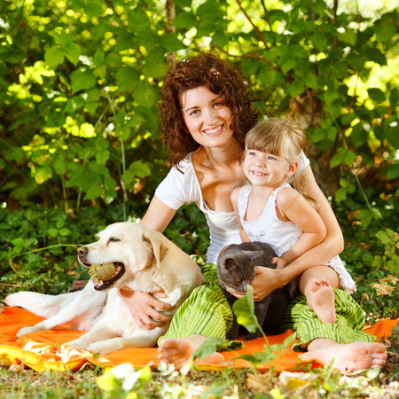 Beautiful mother and daughter relaxing in nature with pets photo