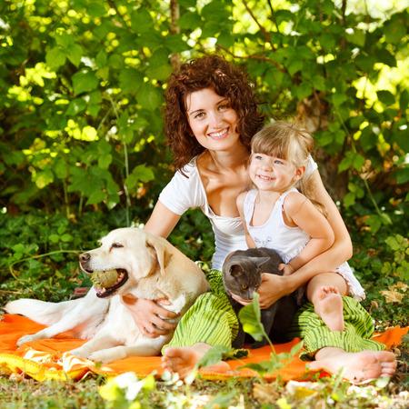 pies descalzos: Hermosa madre e hija se relaja en la naturaleza con los animales domésticos Foto de archivo