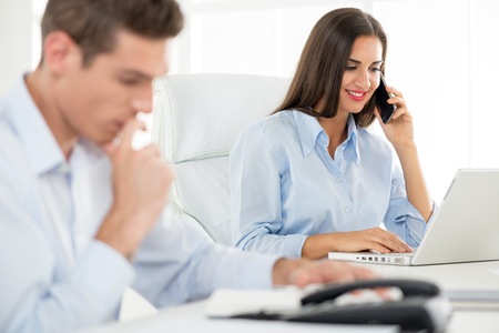 telephoning: Young beautiful businesswoman telephoning in the office. Stock Photo