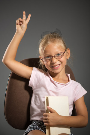 shutting: Cute little girl sitting with book and golding two fingers up. Studio shutting. Grey background. Looking at camera.