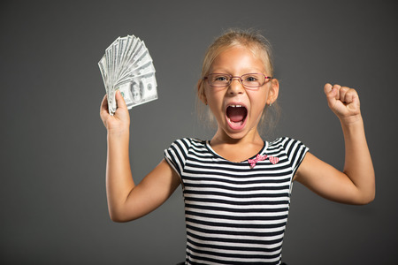 shutting: Pretty happiness little girl holding dollars. Studio shutting. Grey background. Looking at camera
