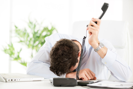 displeased businessman: Tired young Businessman holding telephone and leaning his head on the table in the office.  Stock Photo