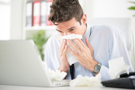 suo: Giovane uomo di affari che soffia il naso mentre si lavora al suo computer portatile in ufficio.