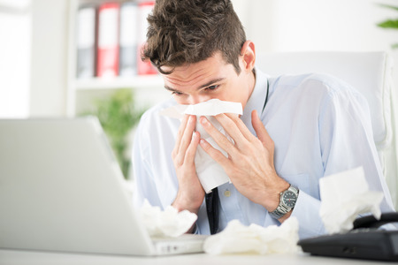 Young business man blows his nose while working at his laptop in the office.