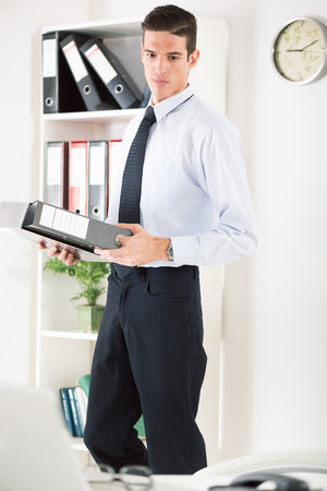 Young thinking Businessman standing in the office and holding binder. photo