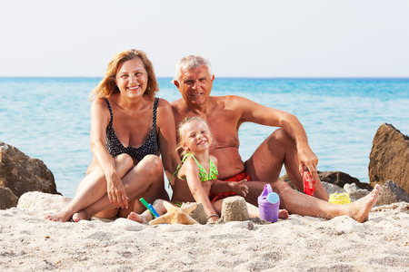 Happy Little girl with grandparents on the beach with bucket and spade photo