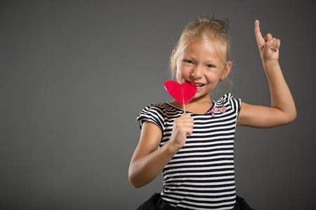 pretty little girl: Pretty little girl smiling and posing with lollipop. Studio shutting. Grey background. Looking at camera.